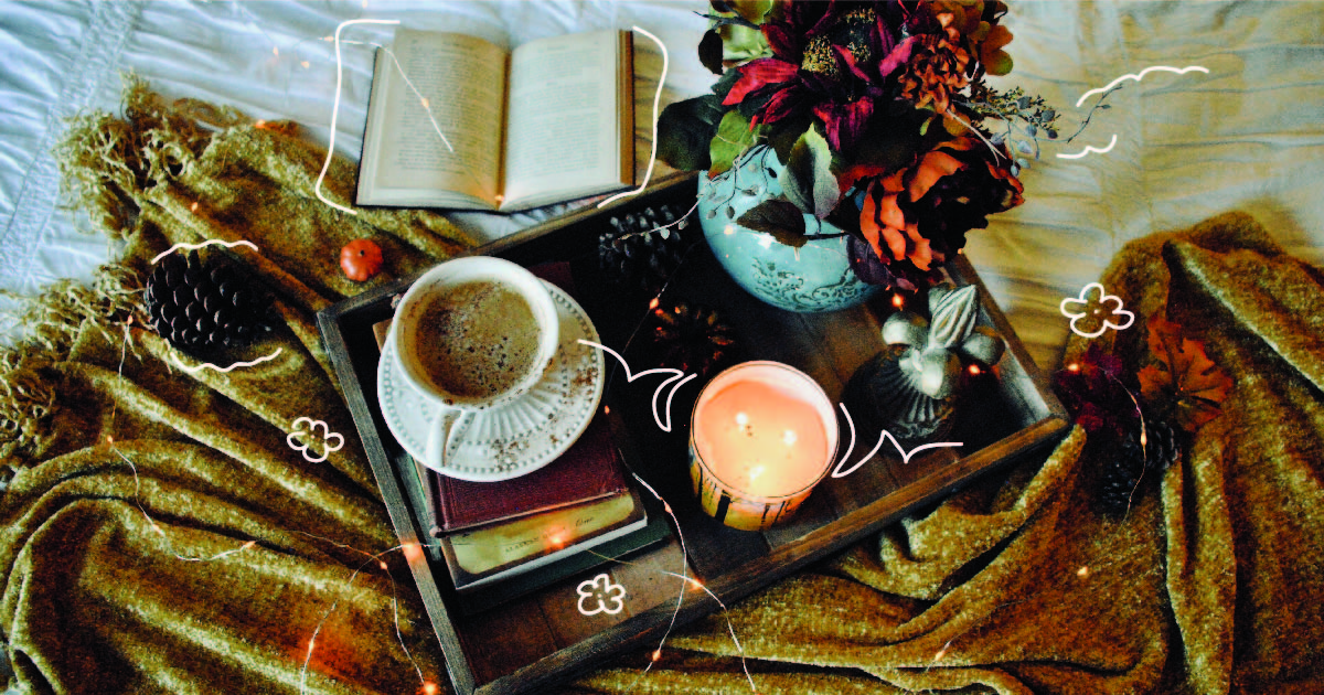 An array of items strewn across a soft blanket: A book, a cup of tea, a candle, a bouquet of flowers, and some decorative pine cones.