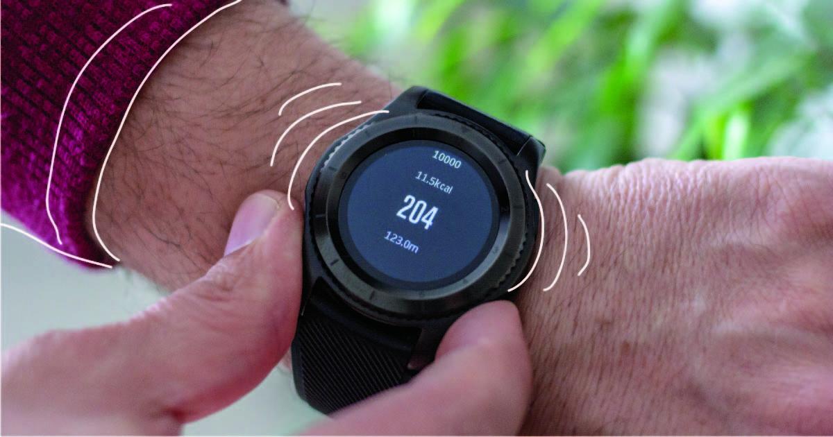A round black pedometer on a person's wrist.
